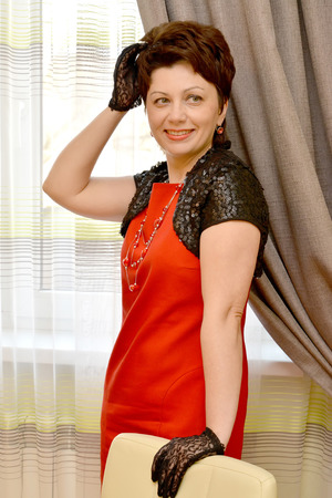 average woman: The joyful woman of average years in black openwork gloves and a bolero costs with the raised hand Stock Photo