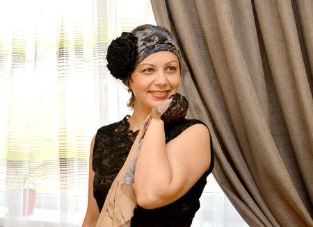 average woman: The joyful woman of average years in a hat with a veil and a scarf in a hand against a window