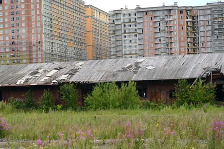 poorly: Old railway workshops against a housing estate under construction. St. Petersburg