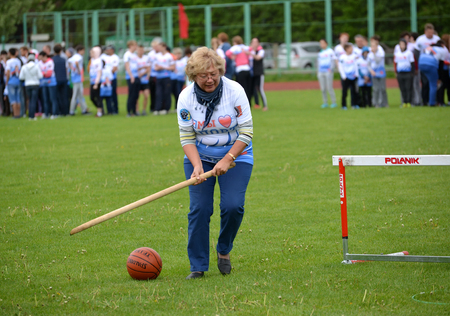 average woman: KALININGRAD, RUSSIA - MAY 15, 2016: The woman of average years rolls before herself a ball by means of a stick at the competitions Cheerful Starts Editorial