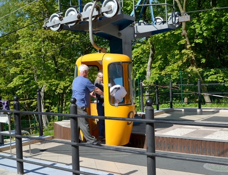 SVETLOGORSK, RUSSIA - MAY 22, 2016: The worker of a ropeway helps the female passenger to leave a cabin Editorial