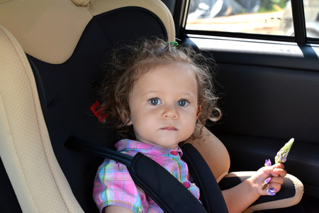 sits on a chair: The two-year-old girl sits in the car in a baby car seat Stock Photo