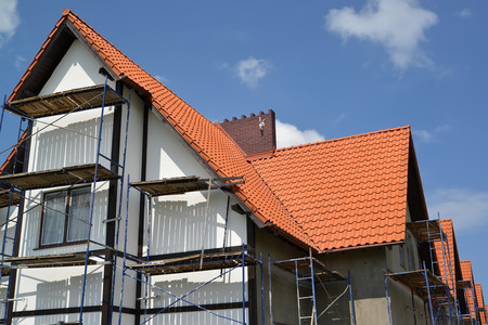 plastered wall: Construction of a house with a red tile roof