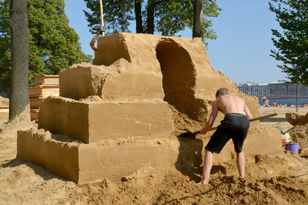 ST. PETERSBURG, RUSSIA - JULY 13, 2014: The man begins work on a sandy sculpture. Annual international festival of sandy sculptures Editorial