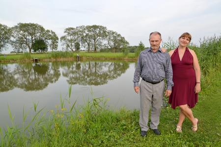age 50 55 years: The married couple costs on the bank of a pond in summer day