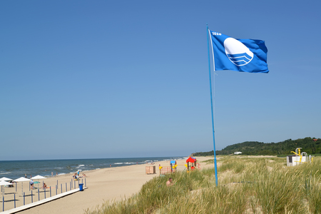 AMBER, RUSSIA - JUNE 27, 2016: The international sign of beaches Blue flag flutters over the city beach, the Kaliningrad region