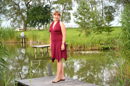 claret: The woman in a summer claret dress stands on a planked footway near a pond
