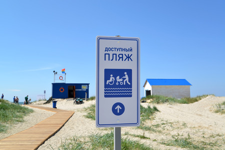 poorly: AMBER, RUSSIA - JUNE 27, 2016: The index Available beach against the background of life-saving station. An inscription at the stand in Russian: The available beach