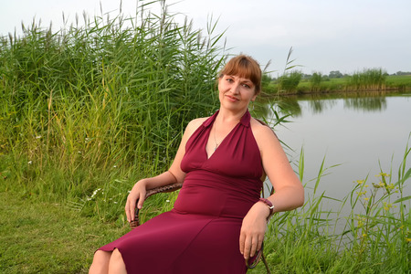 The woman in a summer claret dress sits on the bank of the lake Stock Photo