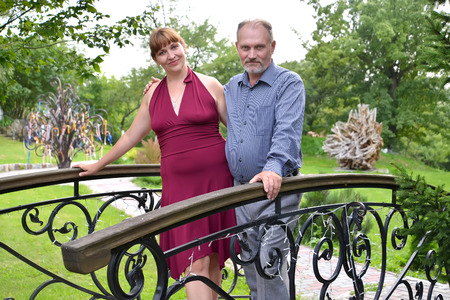 50 55 years: The married couple of average years is installed on the decorative bridge in the park