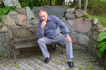 50 to 55 years: The man of average years sits on a decorative bench