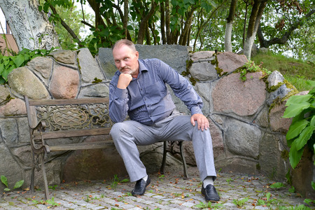 50 to 55 years: The man of average years has a rest on a decorative bench