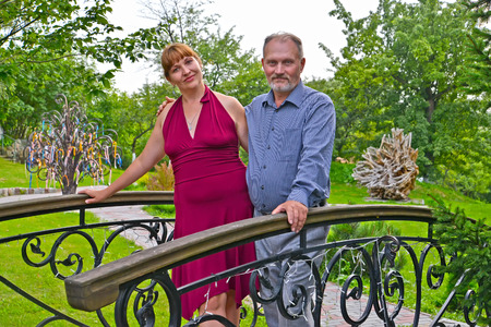 50 to 55 years: The man and the woman stand on the decorative bridge in the park