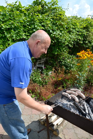 50 to 55 years: The elderly man prepares sausages a grill on a brazier. A picnic  in the country