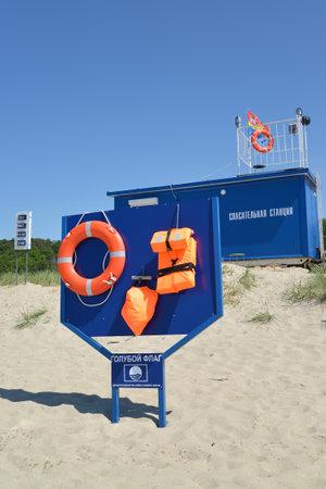 """salvavidas: AMBAR, Rusia - JUNIO 27,2016: El soporte con medios de salvamento sobre la estaci�n de salvar la vida. Una inscripci�n en ruso en el stand de """"Bandera Azul"""", """"estaci�n de salvamento"""""""