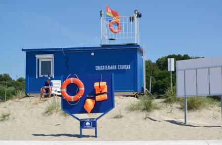 """salvavidas: AMBAR, Rusia - 27 de junio 2016: El soporte con medios de salvamento sobre la estación de salvamento, la playa. Una inscripción en ruso en el stand de """"Bandera Azul"""", """"estación de salvamento"""""""