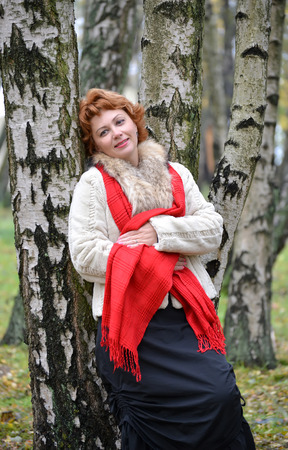 leaned: The woman of average years costs, having leaned against a birch in the wood