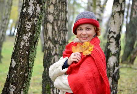 stole: La mujer de los años medios en un sombrero y una estola roja en la madera de abedul