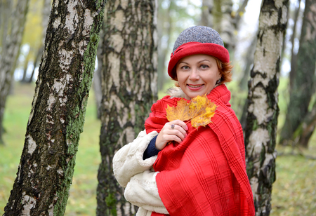 stole: The woman of average years in a hat and a red stole in the birch wood