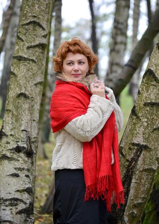 robo: La mujer de los años medios en una estola roja costes entre abedules en el bosque Foto de archivo