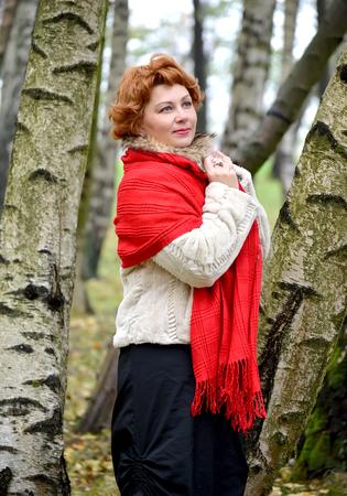 robo: La mujer reflexiva de los años medios en una estola roja costes entre abedules en el bosque