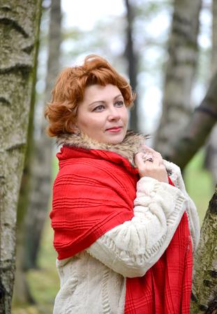 robo: Retrato de la mujer reflexiva de los años medios en una estola roja