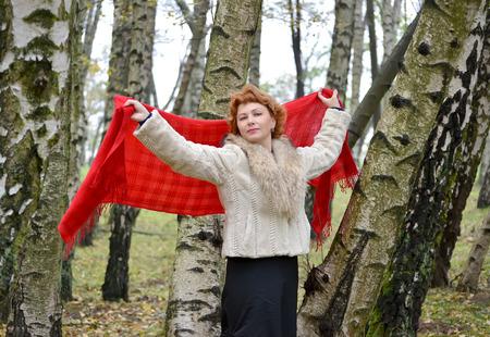 stole: La mujer de los años medios tiene una estola roja en las manos levantadas