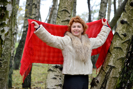 robo: La mujer alegre de los años medios tiene una estola roja en las manos levantadas