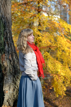 The young woman costs sideways against the background of an autumn tree Stock Photo