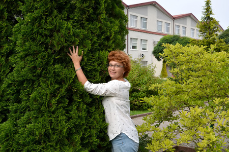 leaned: The woman of average years costs, having leaned against a thuja Stock Photo