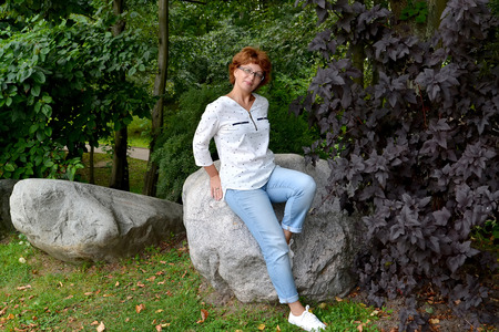wearing spectacles: The woman wearing spectacles sits on a boulder in the park Stock Photo