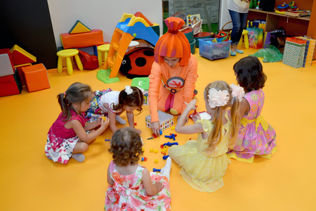 KALININGRAD, RUSSIA - SEPTEMBER 18, 2016: Children play with the animator, sitting on a floor. A holiday in childrens club Editorial