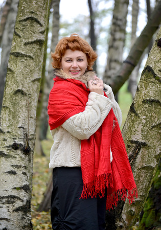stole: The joyful woman of average years in a red stole costs among birches in the wood