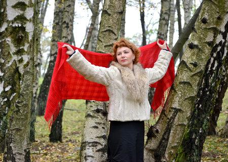 robo: La mujer de los años medios tiene una estola roja en las manos levantadas