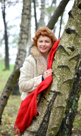 leaned: The cheerful woman with a red scarf costs having leaned against a birch in the wood
