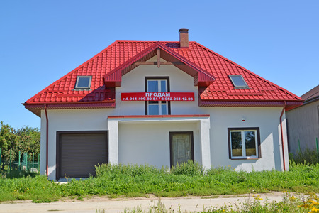 private i: KALININGRAD REGION, RUSSIA - AUGUST 25, 2016: I will sell a new cottage with a banner. An inscription on a banner in Russian: I will sell Editorial
