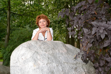 leans on hand: The nice woman of average years stands behind a huge boulder in the park