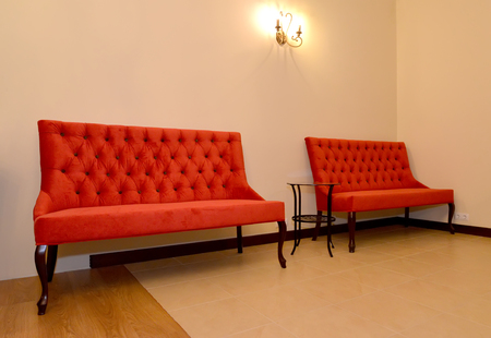 sconce: Two red sofas stand at a wall. Drawing room interior
