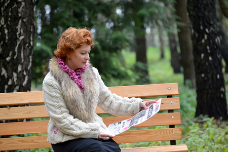 The woman of average years reads the newspaper on a bench in the park Stock Photo