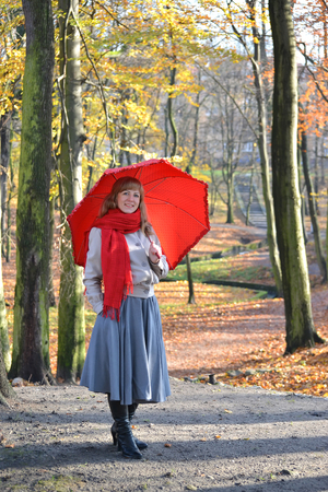 The young woman costs with a red umbrella in the autumn park Stock Photo