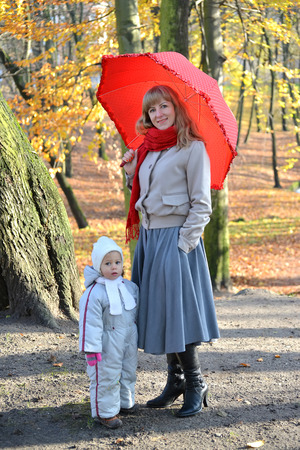 The young woman with the little daughter stand under a red umbrella in the autumn park
