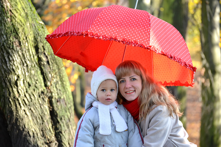 Portrait of the young woman with the little daughter under a red umbrella in the autumn park Stock Photo