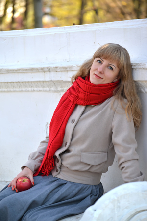 Portrait of the young woman on a bench in the autumn park