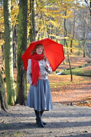 The happy young woman costs with a red umbrella in the autumn park