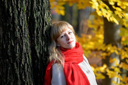 Portrait of the quiet young woman with a red scarf against the background of an autumn tree