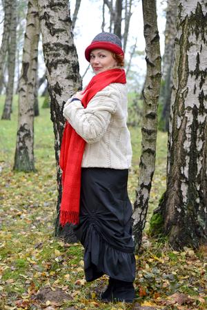 robo: La mujer de los años medios en una estola roja y un sombrero cuesta entre abedules en el bosque