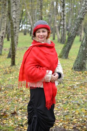 robo: La mujer feliz en una estola roja y un sombrero cuesta entre abedules en el bosque Foto de archivo