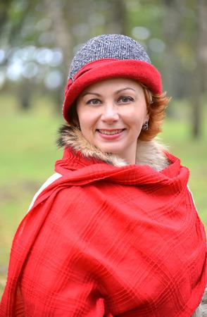 stole: Retrato de la mujer alegre en una estola roja y un sombrero. De cerca