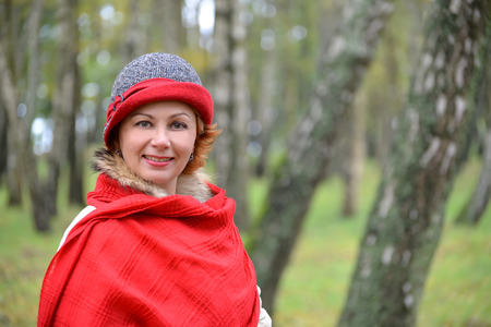 stole: Portrait of the joyful woman in a red stole and a hat in a birchwood