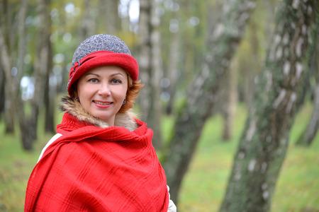 robo: Retrato de la mujer alegre en una estola roja y un sombrero en una madera de abedul